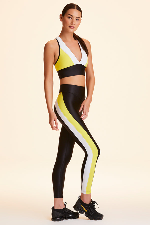 Full body 3/4 view of Alala Women's Luxury Athleisure black/white/yellow color-blocked tight