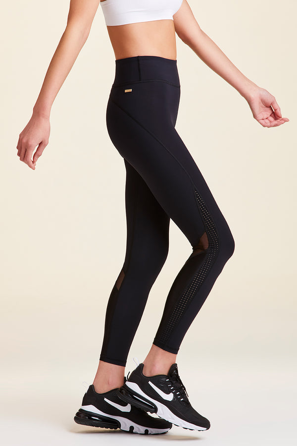Side view of Alala Women's Luxury Athleisure black tight with minimal mesh detail