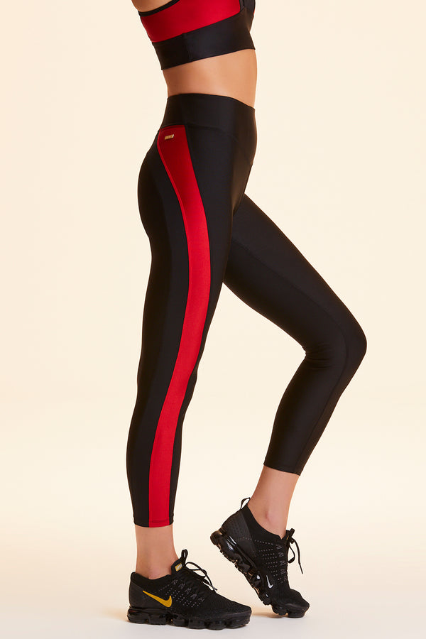 Side view of Alala Women's Luxury Athleisure black/red color-blocked tight