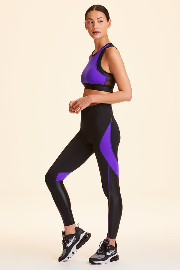 Front and side view of Alala Women's Luxury Athleisure black and purple color-blocked tight