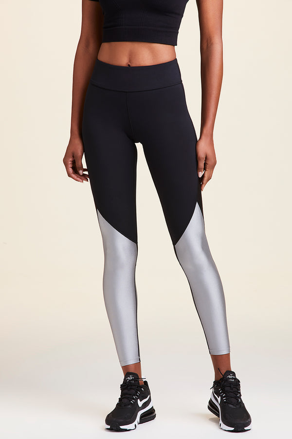 Front view of Alala Women's Luxury Athleisure black and silver tight with mesh paneling on back of knees