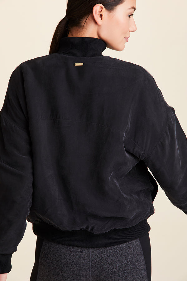 Back view of Alala Women's Luxury Athleisure black woven bomber jacket
