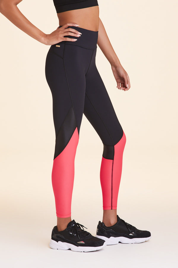 Side view of Alala Women's Luxury Athleisure black and watermelon color-blocked tight