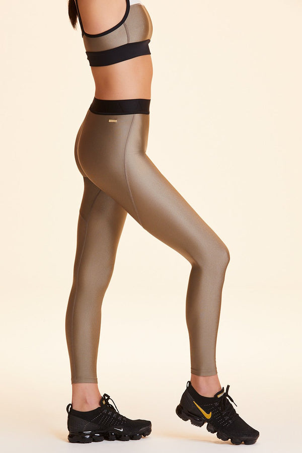Side view of Alala Women's Luxury Athleisure shiny gold tight