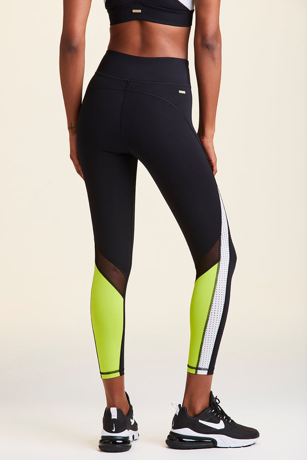 Side view of Alala Women's Luxury Athleisure black, white, and lime 7/8 tight with minimal mesh detail