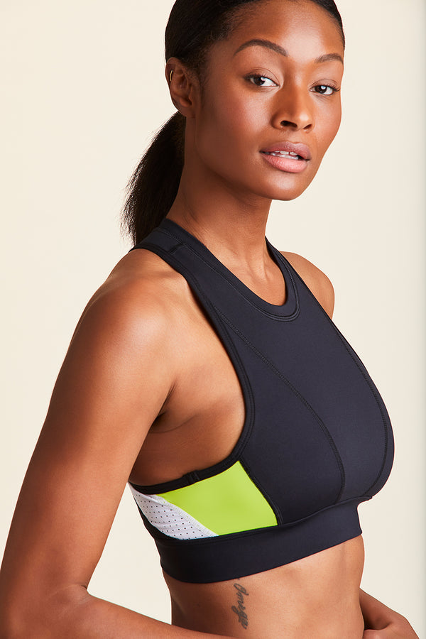 3/4 front view of Alala Women's Luxury Athleisure black, white, and lime color-blocked racerback bra