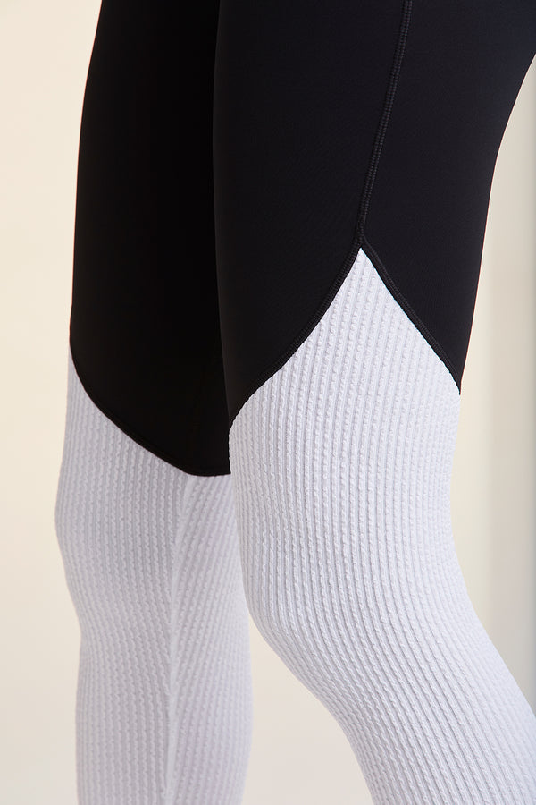 Side view of Alala Women's Luxury Athleisure black and white tights with textured knit fabric and contrasting panels