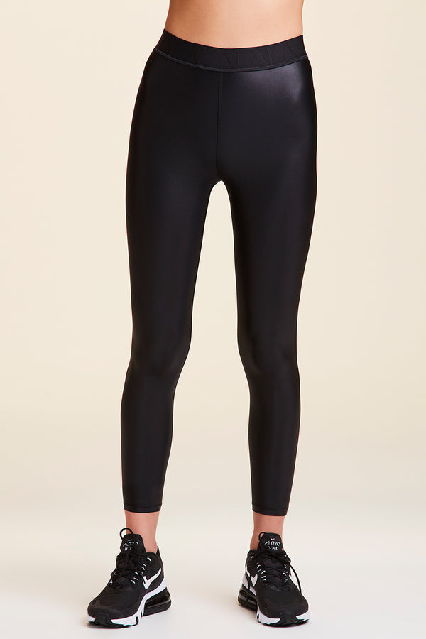 Side view of Alala Women's Luxury Athleisure shiny black tight