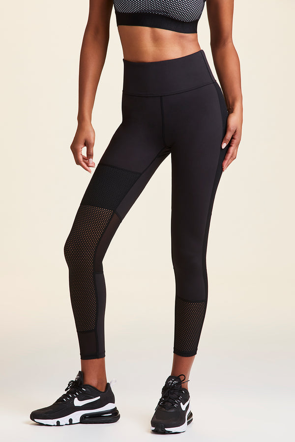 Front view of Alala Women's Luxury Athleisure black tight with mesh detail