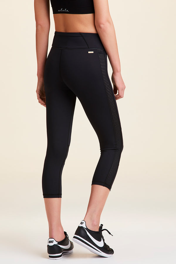 Detailed side view of Alala Women's Luxury Athleisure black cropped tight with white pindot