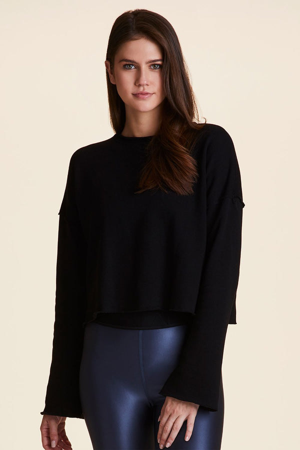 Front view of Alala Women's Luxury Athleisure black cropped sweatshirt with bell sleeves