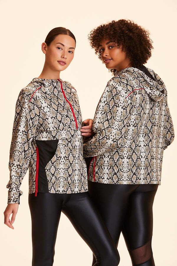 Front and side view of Alala Women's Luxury Athleisure woven anorak in all over snakeprint