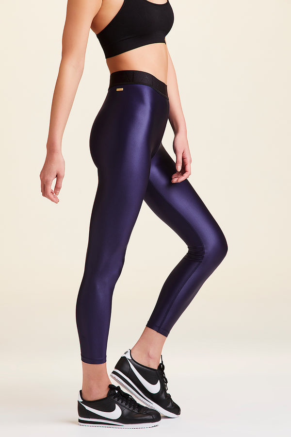 Side view of Alala Women's Luxury Athleisure shiny navy tight