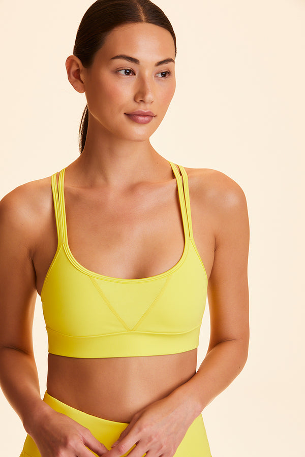 Front view of Alala Women's Luxury Athleisure yellow sports bra with double cross-over straps