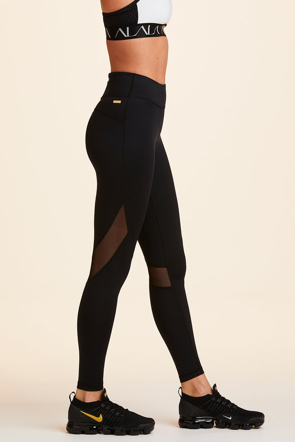 Side view of Alala Women's Luxury Athleisure black tight with mesh paneling on back of knees