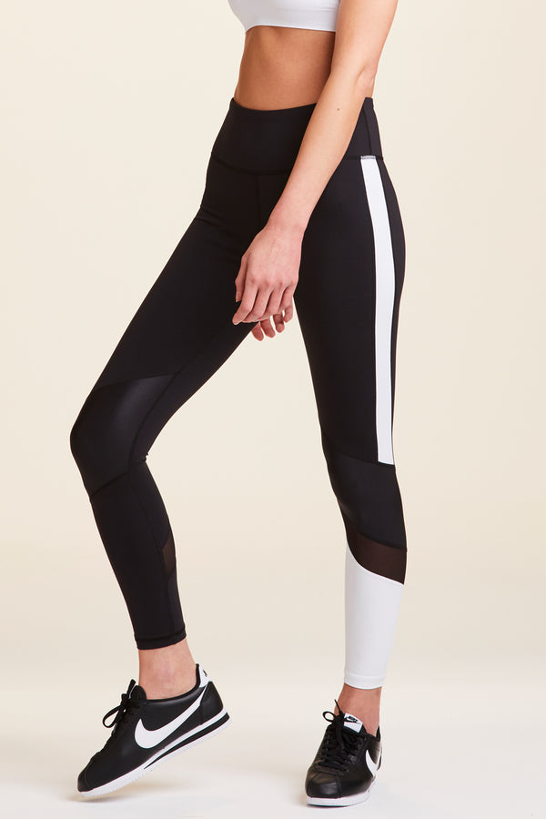 3/4 front view of Alala Women's Luxury Athleisure black and white colorblocked tight
