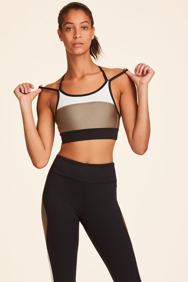 Front view of Alala Women's Luxury Athleisure blocked sports bra with criss-crossed straps in gold, white, & black