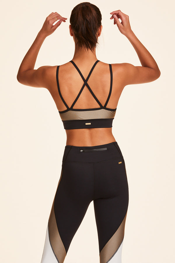 3/4 view of Alala Women's Luxury Athleisure blocked sports bra with criss-crossed straps in gold, white, & black