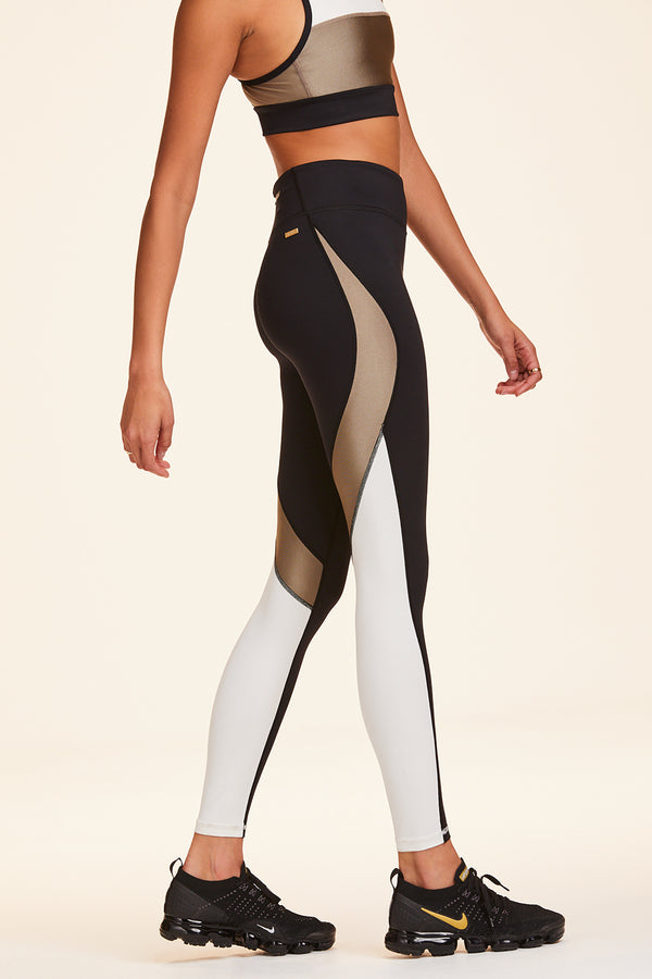 Side view of Alala Women's Luxury Athleisure black, white, and gold color-blocked tight