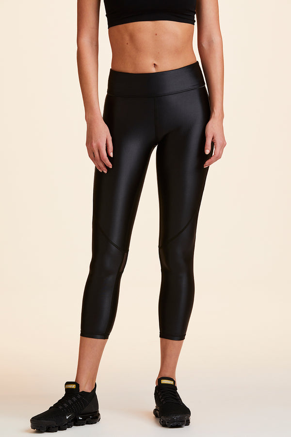 Side view of Alala Women's Luxury Athleisure cropped shiny black tight with mesh paneling on back of knees.
