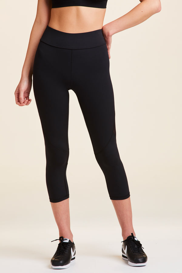 Side view of Alala Women's Luxury Athleisure cropped black tight with mesh paneling on back of knees.