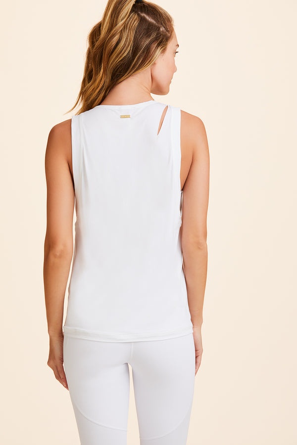 3/4 view of Alala Women's Luxury Athleisure white tank with minimal slicing detail.