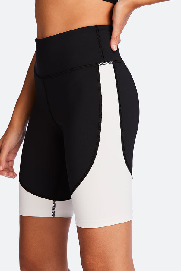 Side view of Alala Women's Luxury Athleisure black and white biker short