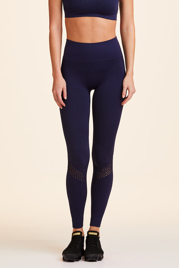Side view of Alala Women's Luxury Athleisure navy blue seamless tight with mesh detailing
