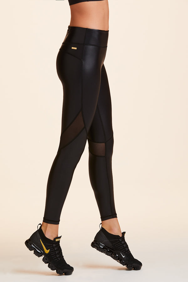 Front view of Alala Women's Luxury Athleisure shiny black tight with mesh paneling on back of knees