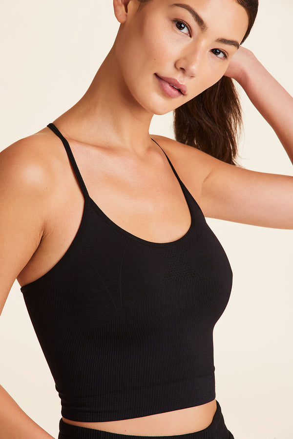 Side view of Alala Women's Luxury Athleisure black seamless tank with cross over back strap detailing.