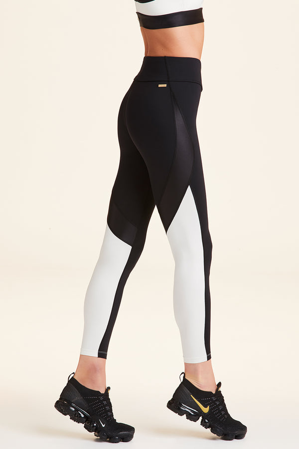 Side view of Alala Women's Luxury Athleisure black and cream color-blocked tight