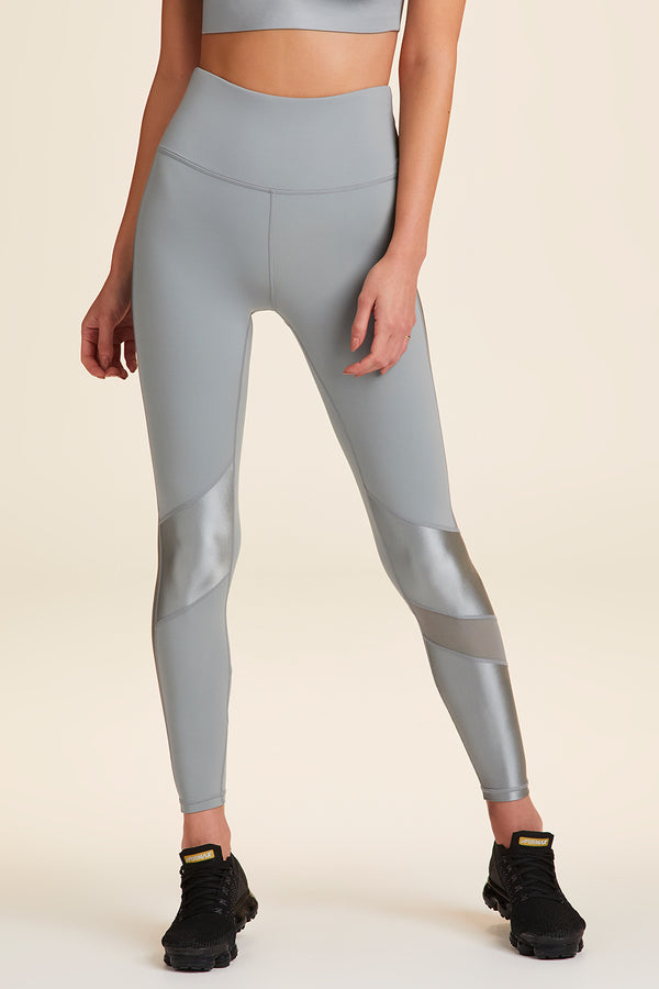Side view of Alala Women's Luxury Athleisure grey tight with shiny gunmetal detail