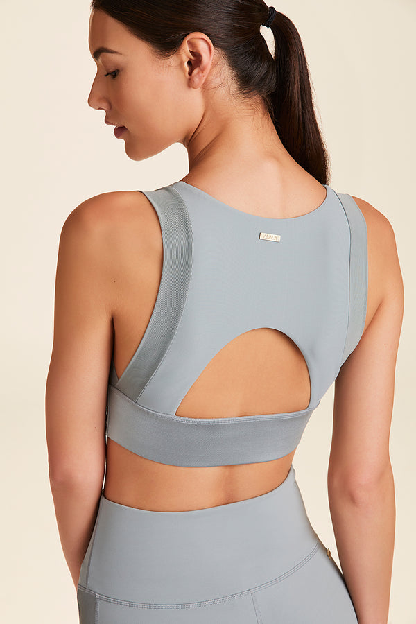 3/4 front view of Alala Women's Luxury Athleisure grey sports bra with open back detail