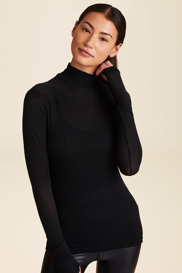 Front view of Alala Women's Luxury Athleisure black ribbed turtleneck