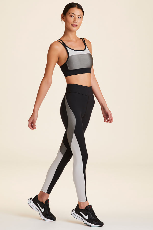 Front view of Alala Women's Luxury Athleisure blocked sports bra with criss-crossed straps in silver, white, & black