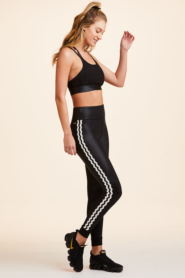 Side view of Alala Women's Luxury Athleisure shiny black tight with side stripe detail