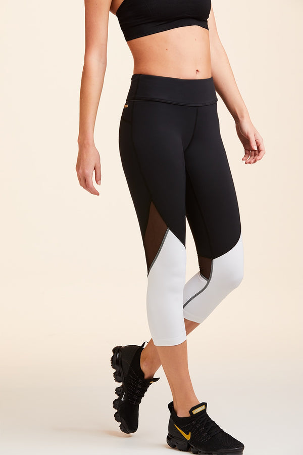 Front and side view of Alala Women's Luxury Athleisure cropped black and white tight with mesh paneling on back of knees.