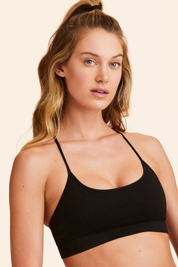 Front view of Alala Women's Luxury Athleisure black seamless bra with cross over back strap detailing
