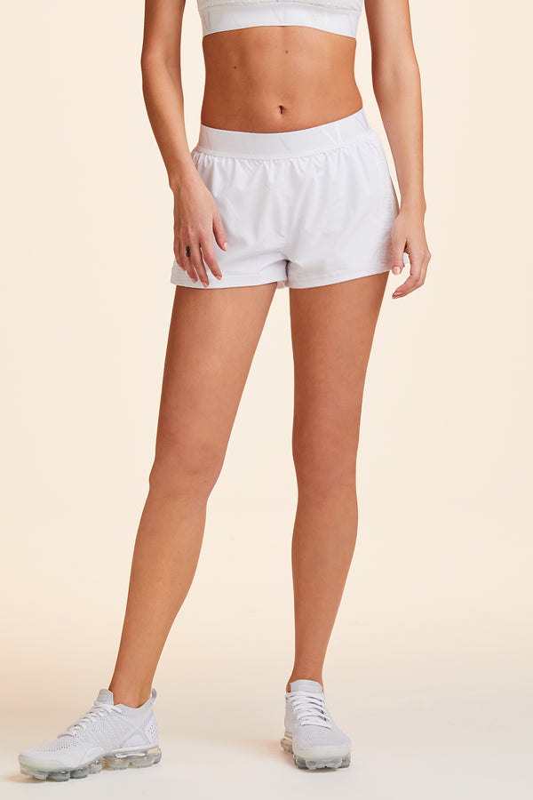 Side view of Alala Women's Luxury Athleisure white shorts