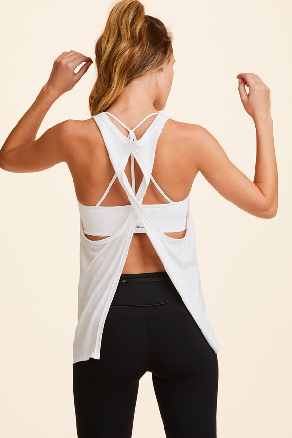 Front view of Alala Women's Luxury Athleisure white asymmetrical tank with split back panel