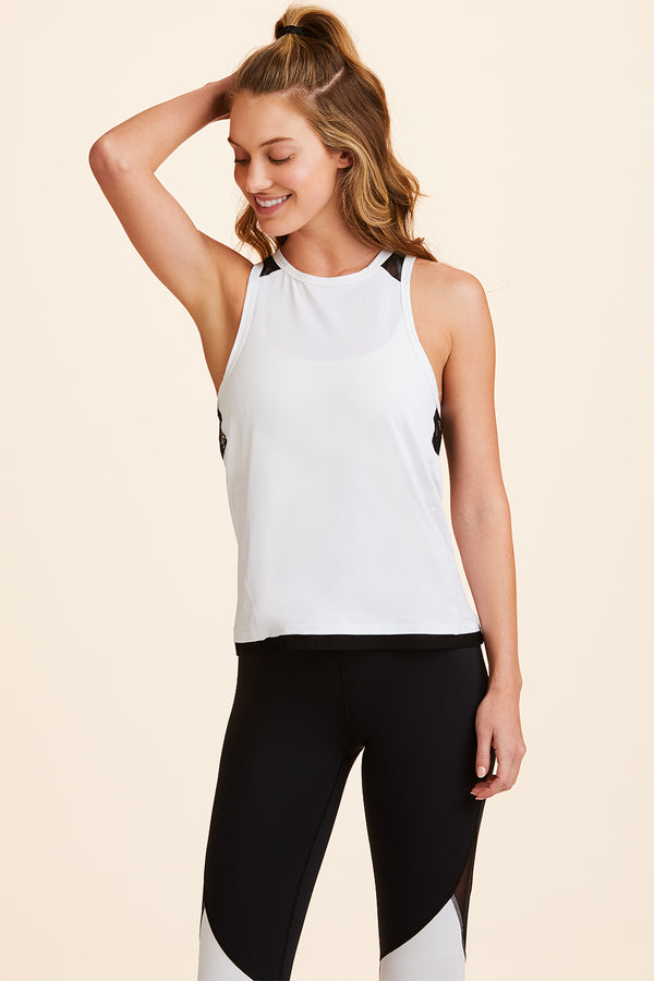 Front view of Alala Women's Luxury Athleisure white tank with black mesh detail