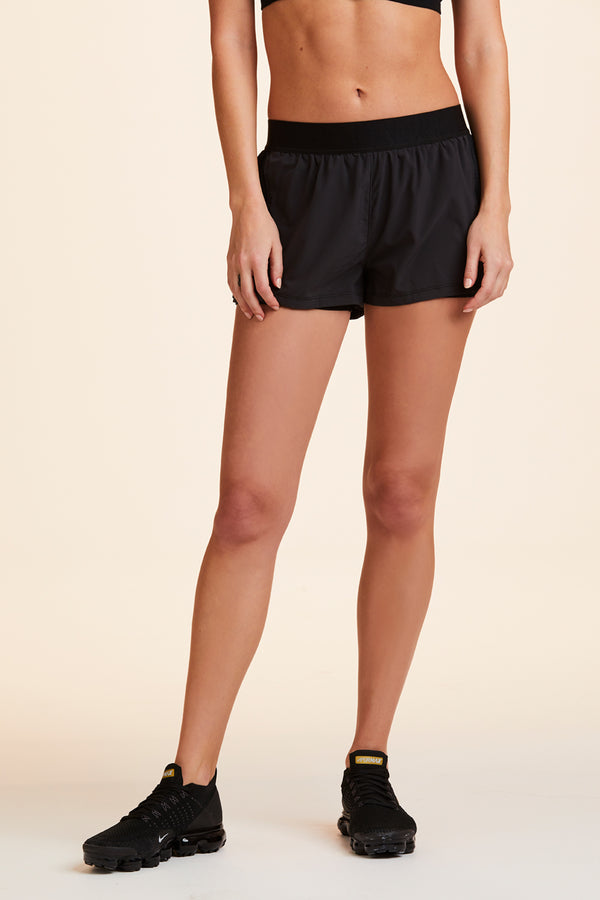 Side view of Alala Women's Luxury Athleisure black shorts