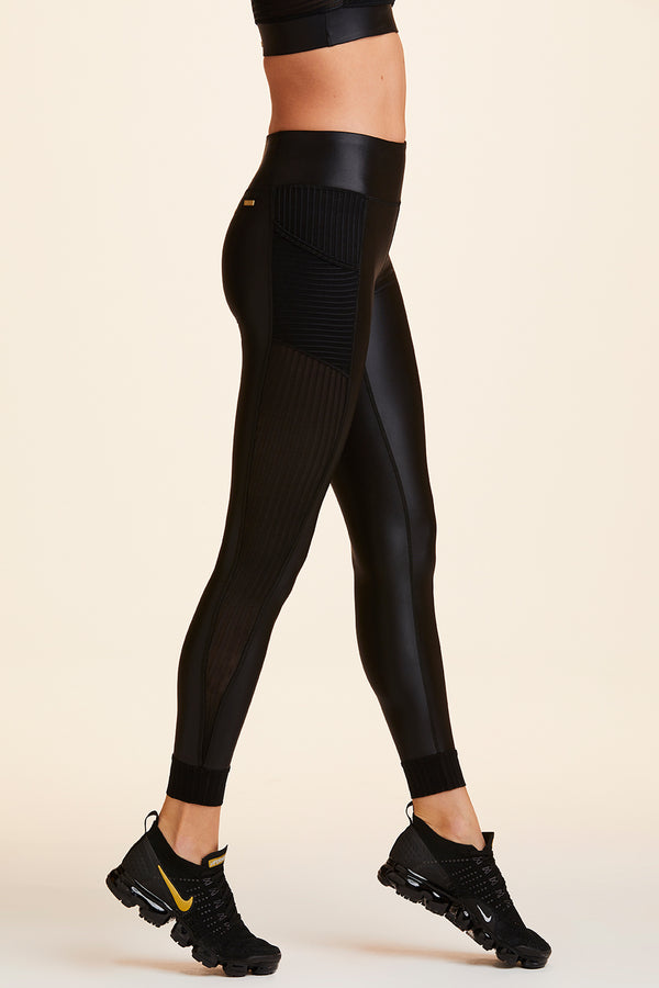 Side view of Alala Women's Luxury Athleisure shiny black tight with sheer ribbed detail