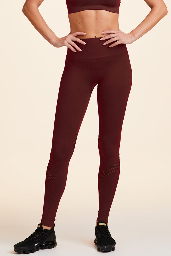 Side view of Alala Women's Luxury Athleisure burgundy  seamless tight with mesh detailing