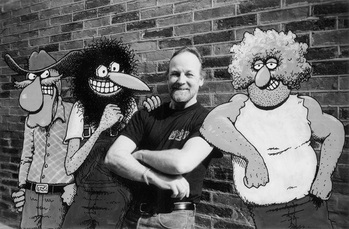 Gilbert Shelton standing with The Freak Brothers
