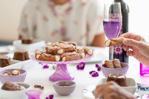 Two women sit at a table filled with gluten free sweets, fresh flowers, a bottle of wine and glasses. One woman holds a gluten free cannoli in her hand.