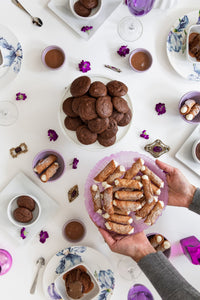Overhead shot of a woman placing a purple dish of gluten free cannoli on a table filled with gluten free sweets, fresh flowers and decorative plates.
