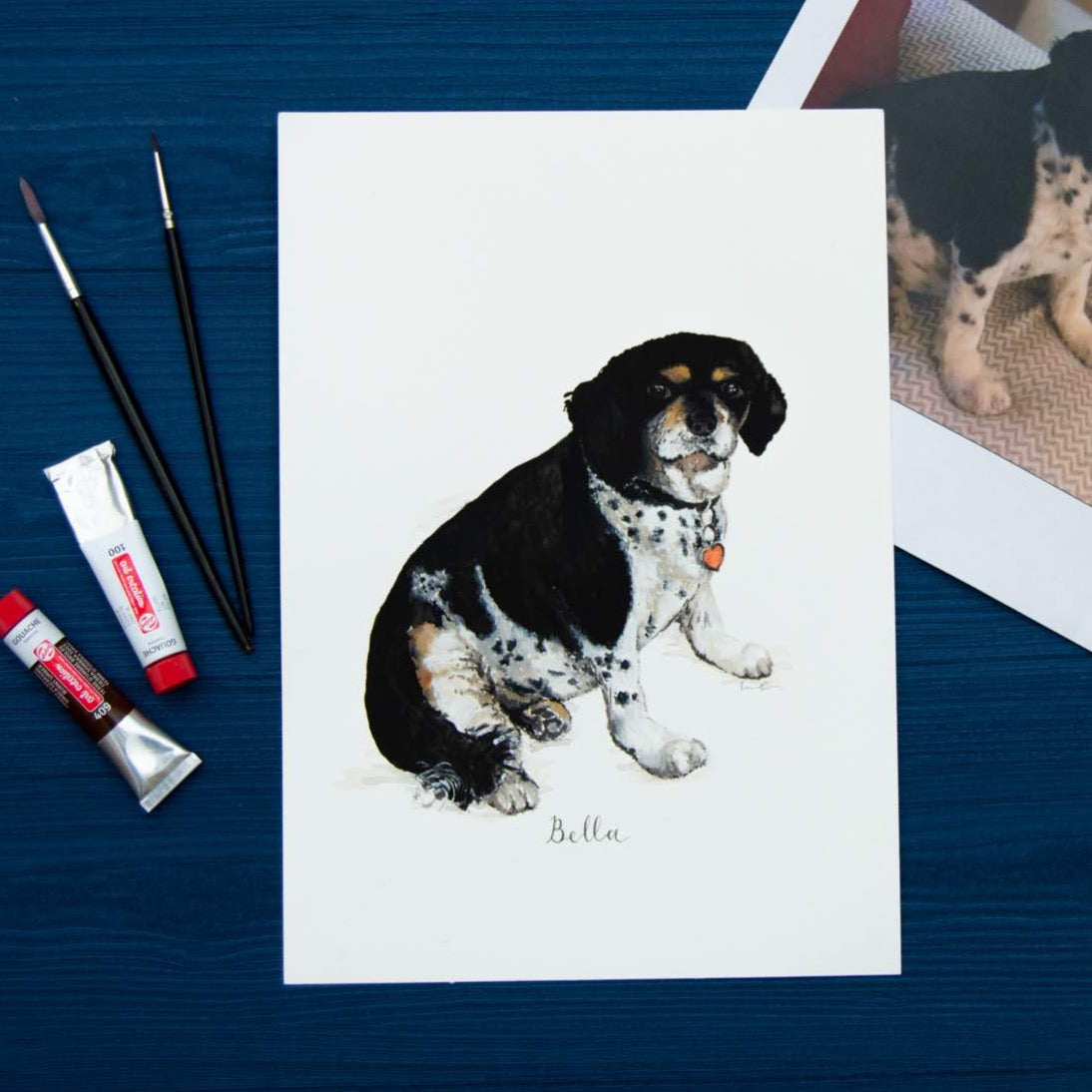 Painting of a black and white dog on a blue background with paint brushes and two tubes of paint.
