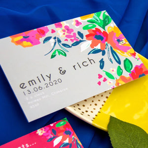 Grey landscape wedding invitation with multicolour floral pattern to one side on bright blue background.