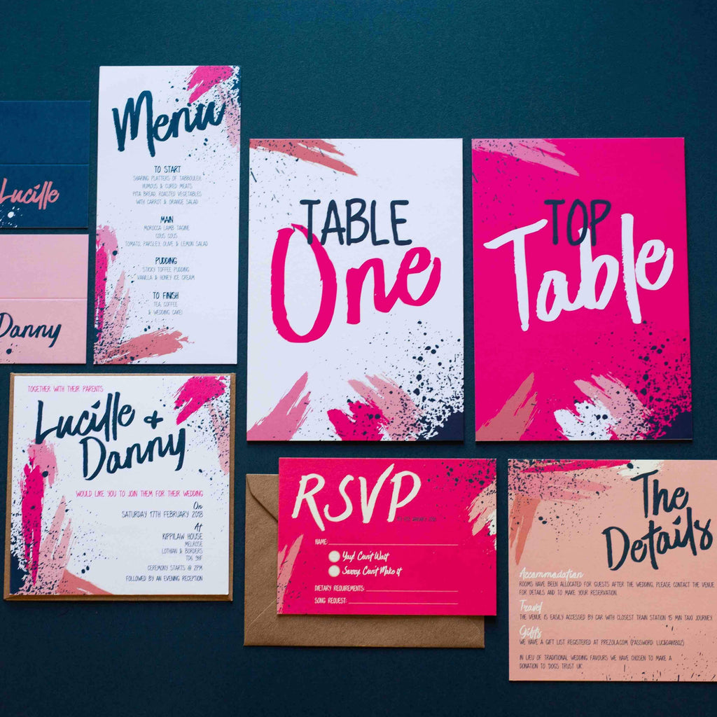 Contemporary pink and navy paint splatter wedding stationery flatlay on surface.  Wedding invitation, rsvp, details card, menu, place names and table numbers.